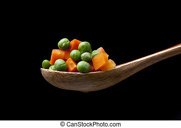 Mixed vegetables on wooden spoon.