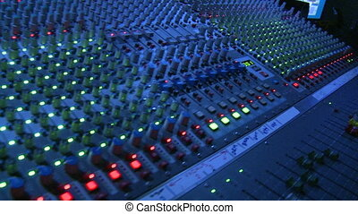 Sweeping across the master controls of a professional sound mixing board.