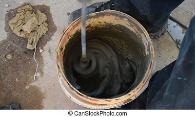 Mixing cement glue or mortar with a long drill. Worker...