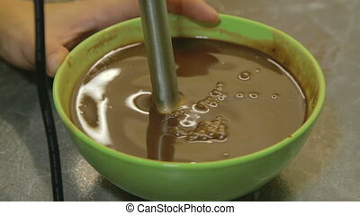 Mixing chocolate glaze in blender - closeup, shooting in the...