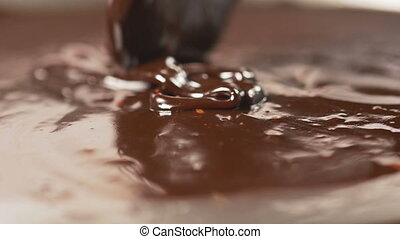 Mixing chocolate with a spoon - Mixing delicious melted...