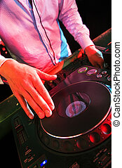 Mixing DJ - The hands of a DJ on a turntable in a nightclub