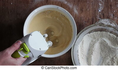 Mixing dough with electric mixer. Cooking at home.
