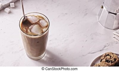 Mixing freshly prepared ice coffee drink with milk by spoon...