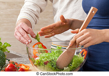 Mixing salad - Husband disturbing his wife in making a salad