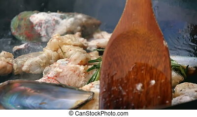 Mixing the seafood dish with paddle in pan. Close up. Slow...