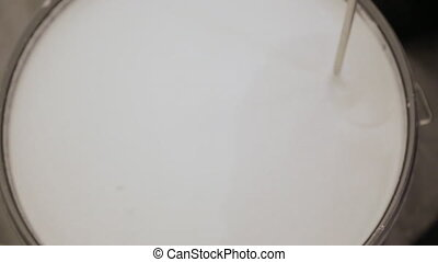 Mixing white paint in a bucket