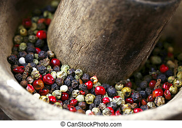 Mixture of peppers in a antique wooden mortar