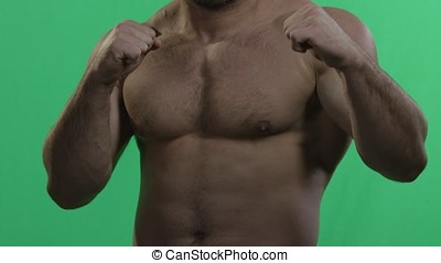 MMA fighter on a green screen. Muscular man on green screen. Green background. Man punching gesture