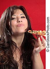 Mmmm woman enjoying pizza - A woman with dark brown hair is...
