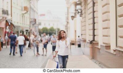 mnóstwo, kobieta shopping, mówiąc, ruchomy, młody, telefon, ulica
