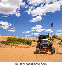 Moab off road trail under sunny sky with clouds. Vehicle on...