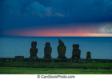 Moai shilouette in the Ahu Tahai at sunset against deep blue...