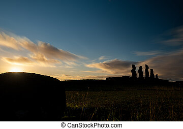 Moai shilouette in the Ahu Tahai at sunset, profile view -...