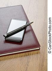 mobiele telefoon, pen, aantekenboekje