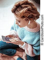 Nice attractive woman looking at the smartphone screen
