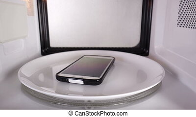 Mobile cell phone heating in the microwave oven inside view.