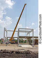 Mobile crane is operating and lifting concrete joist. Landscape transform into urban area.