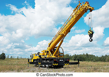 mobile crane with risen boom outdoors - yellow automobile...