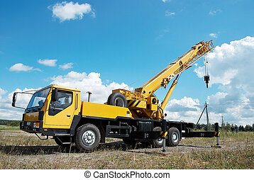 mobile crane with risen boom outdoors - yellow automobile ...