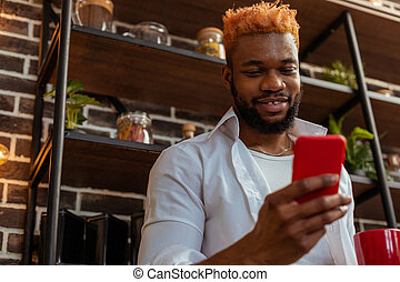Positive African American man holding his smartphone