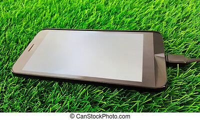 mobile, isolé, téléphone, arrière-plan vert, herbe, charger