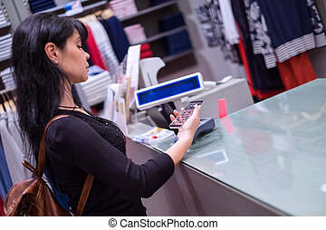 Mobile payment. Girl pays to shop using mobile phone