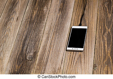 Mobile phone and charger cable plugged in on a wooden desk