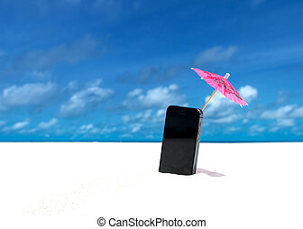Mobile phone and cocktail umbrella on the beach with the sea...