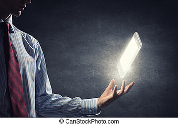 Mobile phone - Close up of businessman hand holding glowing...