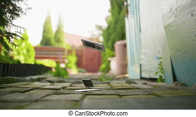 Mobile phone falls and breaks on the concrete ground in slow motion