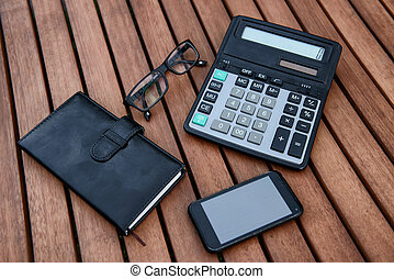 Mobile phone, glasses, calculator, notepad on wooden table. Business acsessorize concept.