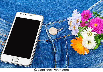Mobile phone in pocket of blue jeans with flowers