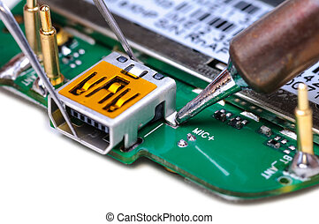Electronic technician repairs mini USB socket on mobile phone circuit board. Close-up with selective focus and Shallow Depth of Field. Isolated on white background.