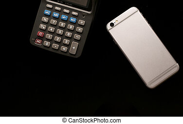 mobile phone with calculator use in business office black background