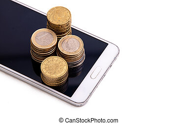 mobile phone with metallic coins isolated on white