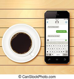 Mobile phone with sms chat on screen and coffee cup on wooden table