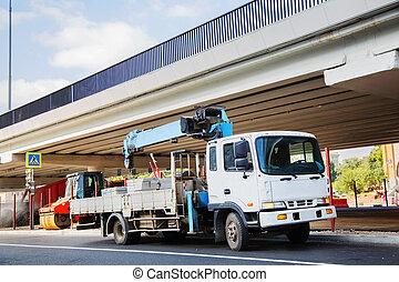 A White flatbed truck with blue crane arm is in the parking lot under bridge, unloads concrete blocks.