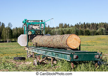 Mobile sawing equipment for logs in the open air. Rural landscape on a sunny day