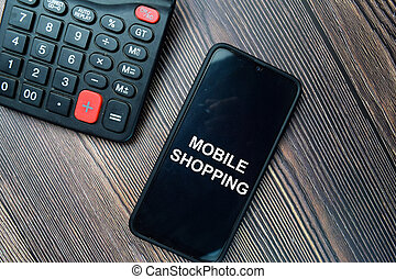 Mobile Shopping write on Smartphone isolated on office desk.