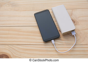 Mobile smart phones charging with power bank on desk and...