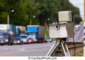 mobile speed camera device working on summer daytime road with blurry traffic in background
