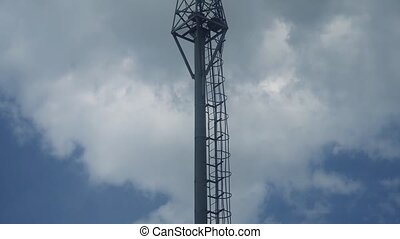 Mobile telecommunication tower on the background of the rainy clouds