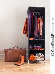 Mobile wardrobe with clothing and leather suitcase