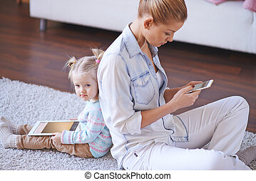 Mobility - Little girl and young woman with gadgets sitting...