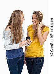mobiltelefon, medan, holdingen, skratta, student, två, kvinnor