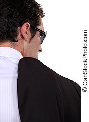 Mobster carrying his jacket over his shoulder