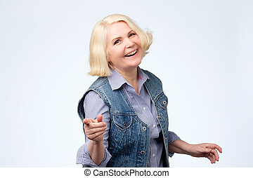 Mature woman pointing finger and toothy smile. Studio shot