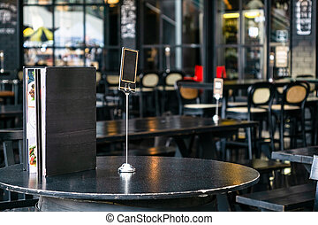 Mock up blank cover menu frame on the blurred background of outdoor coffee and restaurant terrace with tables and chairs .