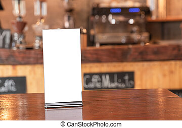 Mock up Label the blank menu frame in coffee shop, Stand for booklets with white sheets paper acrylic tent card on wooden table cafeteria blurred background can inserting the text of the customer.
